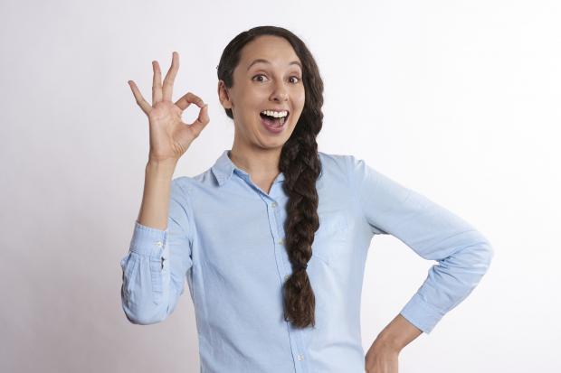 девушка с длинной косой показывает ок