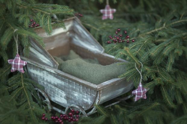 на новогодней елке висит игрушка в виде детской коляски