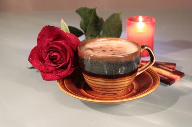 ароматизированная свеча стоит рядом с чашкой фое и красной розой