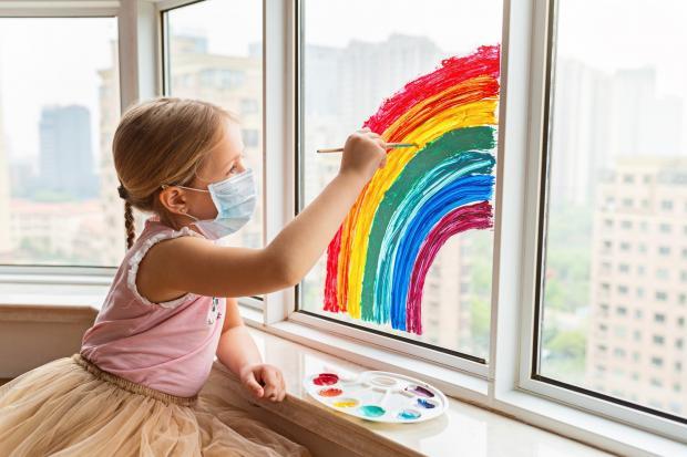 девочка в маске рисует радугу на стекле