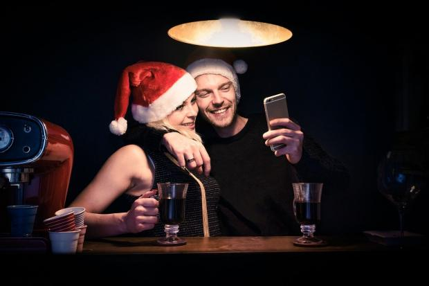 влюбленные в колпаках Деда Мороза пьют кофе