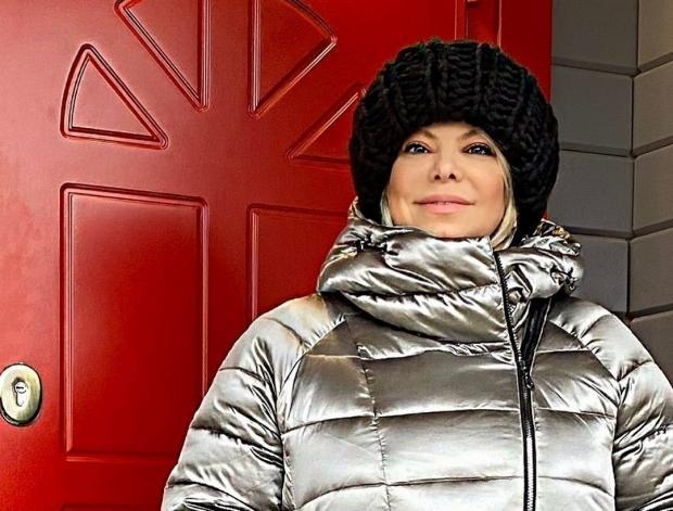 Яна Поплавская в серебристой куртке и черной шапке