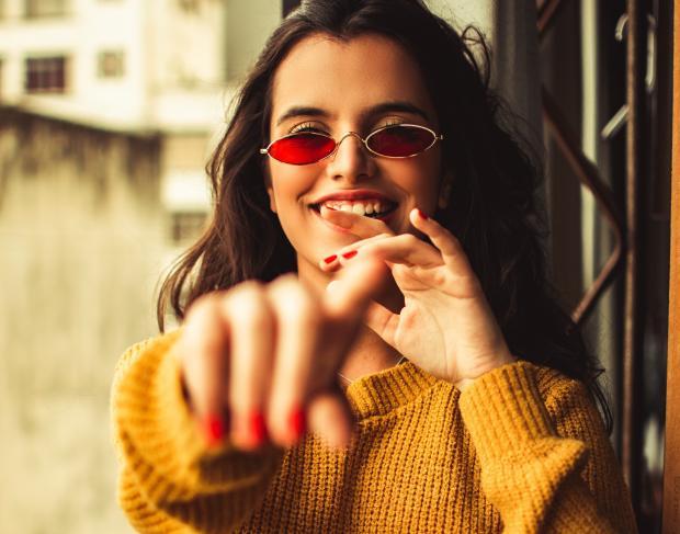 Девушка с темными волосами в желтом свитере и красных очках
