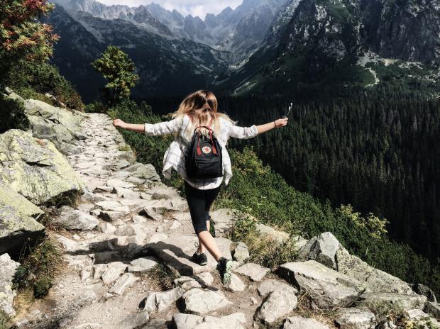 Девушка с рюкзаком гуляет в горах