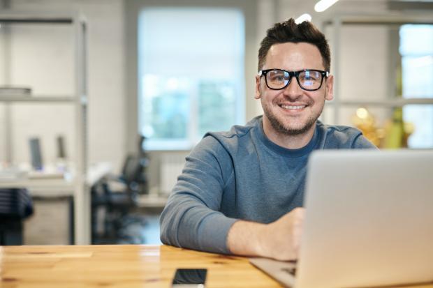 Мужчина в сером свитере и очках улыбается сидя за компьютером