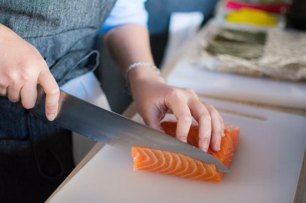 Повар режет рыбу