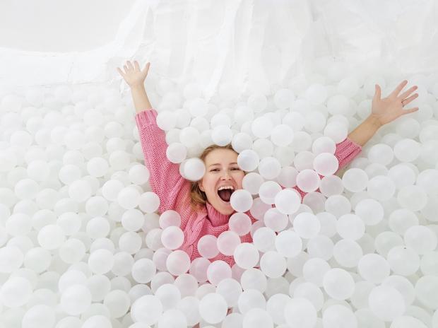 девушка купается в пластиковых шариках