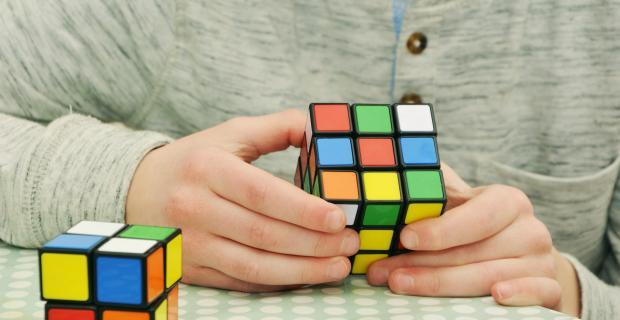 мужчина собирает кубик Рубика
