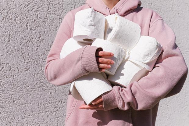 девушка в розовом худи держит туалетную бумагу