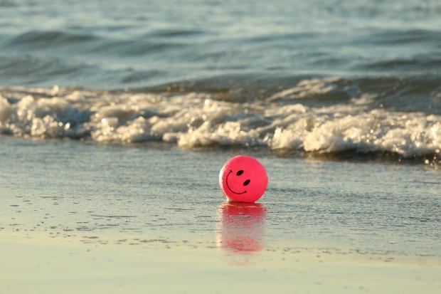 красный мяч с улыбкой на пляже
