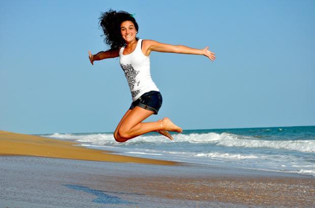 девушка в прыжке на берегу моря