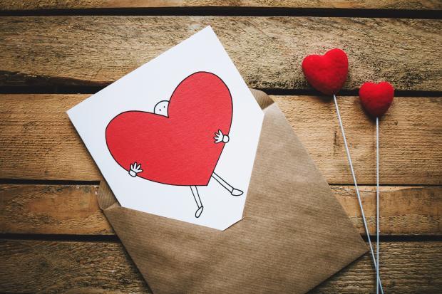 Открытка с рисунком в виде сердца на деревянной поверхности