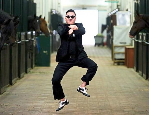 Мужчина в черном костюме танцует в конюшне