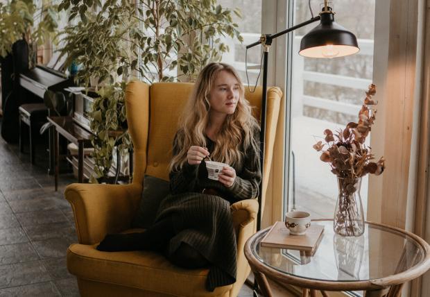 Девушка сидит в кресле с чашкой напитка в руках