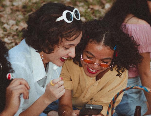 Две девушки смеются смотря в телефон