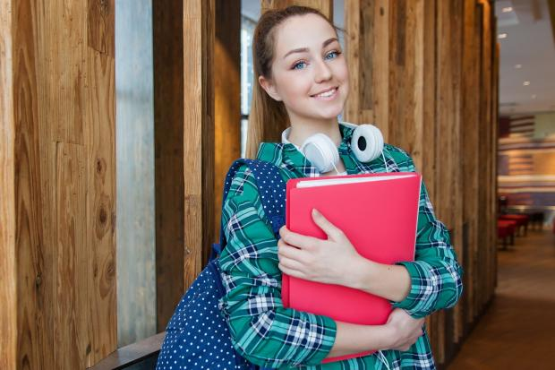 улыбающаяся девушка с наушниками и папкой