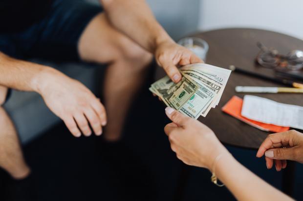 Мужчина передает деньги девушке