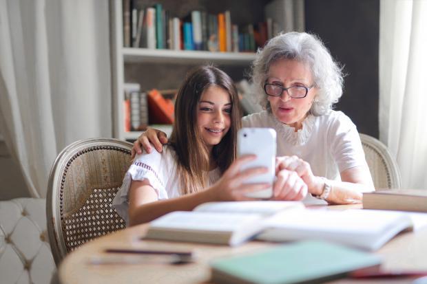 Молодая девушка показывает телефон пожилой женщине