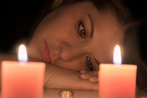 девушка печально смотрит на обручальное кольцо рядом с горящими свечами