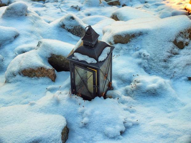 на заснеженных камнях стоит фонарь