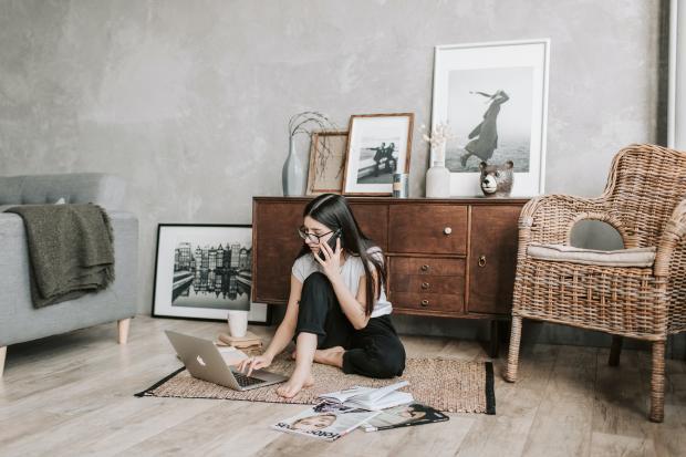 Девушка в белой футболке и черных брюках сидит на полу