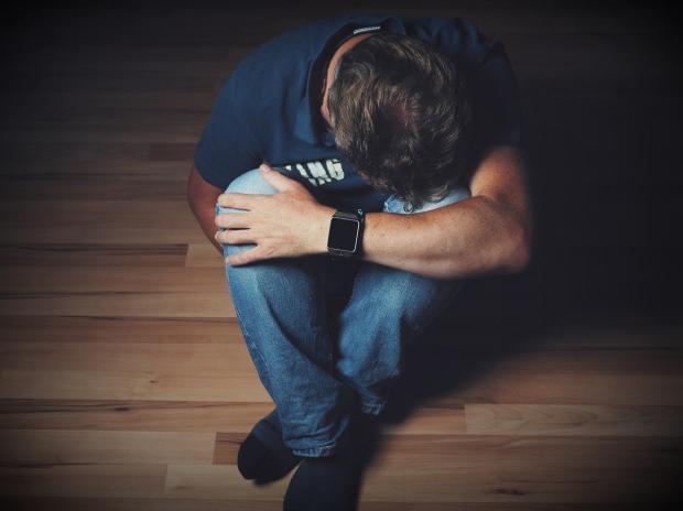 мужчина в отчаянии сидит на полу скрестив ноги