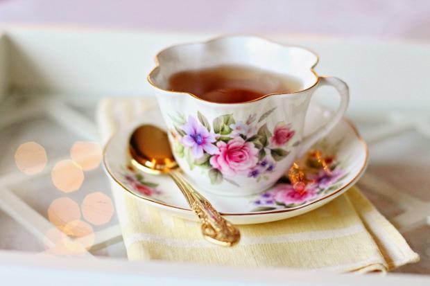 чай к красивой чашке с блюдцем и золоченой ложечкой