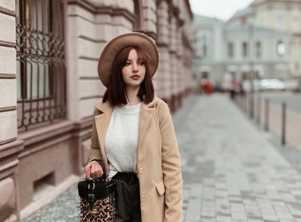 Девушка в коричневом пальто и шляпе идет по улице