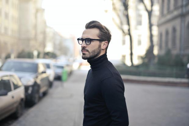 молодой мужчина в черном свитере и очках
