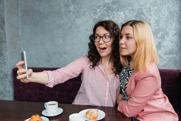 девушки в кафе делают селфи