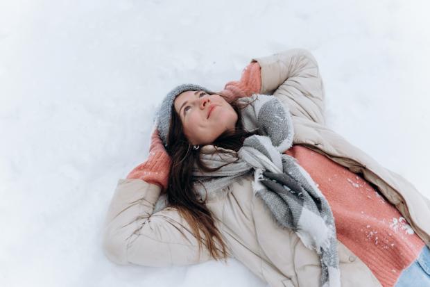 Девушка в белой куртке и розовом шарфе лежит на снегу