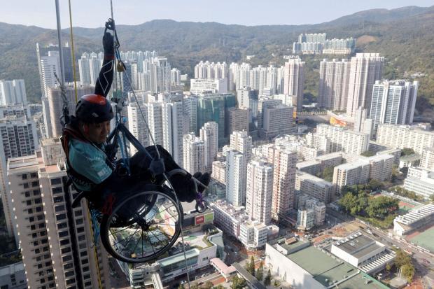 Мужчина на инвалидной коляске на небоскребе