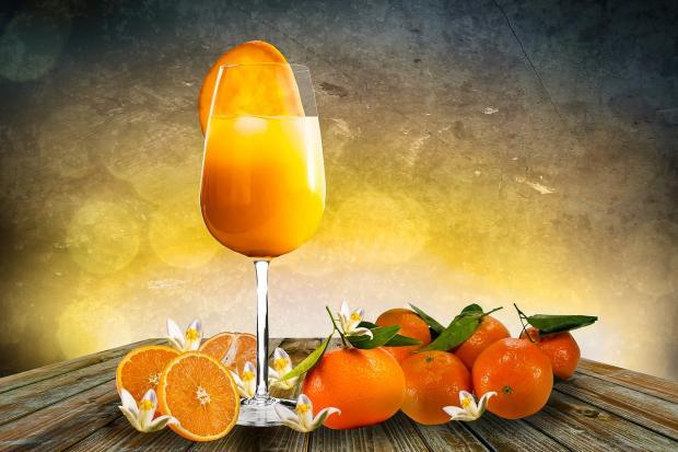 на столе стоит бокал мандаринового сока в окружении фруктов