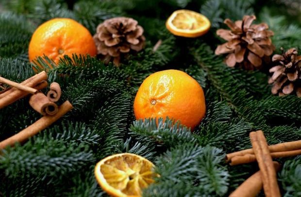 елку украшают мандарины с шишками и палочками корицы