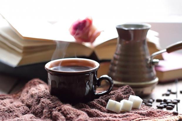 кофе в турке и чашке рядом с раскрытой книгой