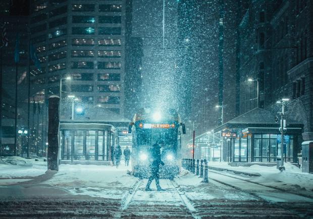 человек идет по заснеженной улице