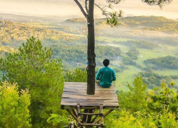 Мужчина в зеленой кофте сидит на деревянном помосте на высоте