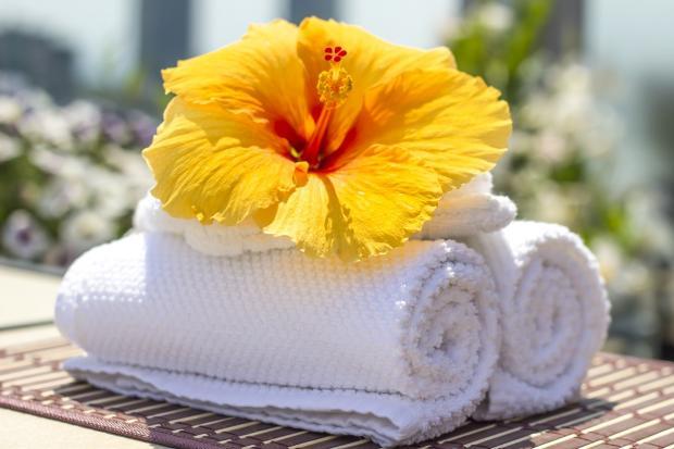 да двух свернутых рулоном белых полотенцах лежит яркий желтый цветок гибискуса