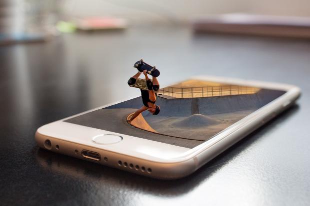 молодой человек на сейте делает трюк на экране телефона