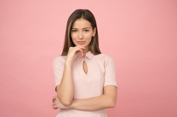 Девушка в бежевой блузе на розовом фоне