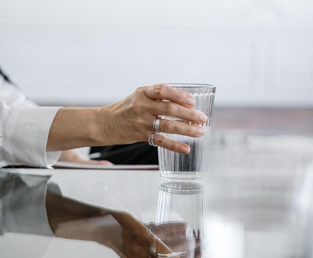 Женщина держит в руке стакан с водой