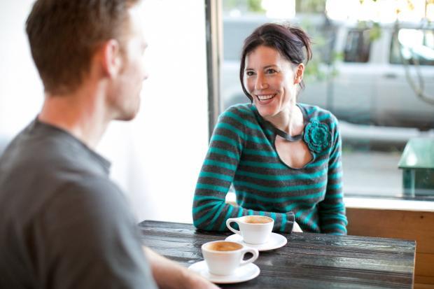 девушка улыбается парню в кафе