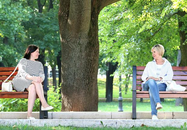 две женщины сидят на скамейках в парке и общаются
