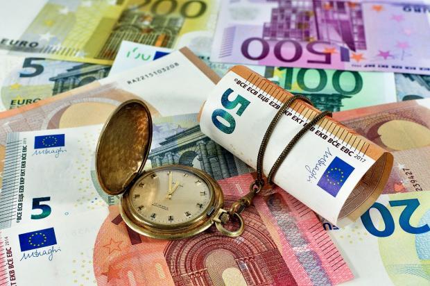 часы лежат на груде банкнот