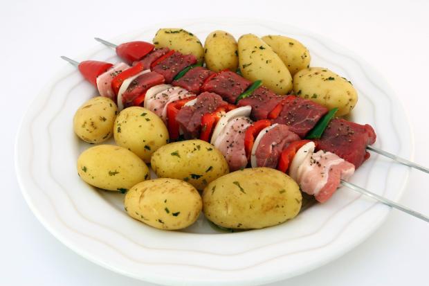 картофель и мясо на шампурах в тарелке