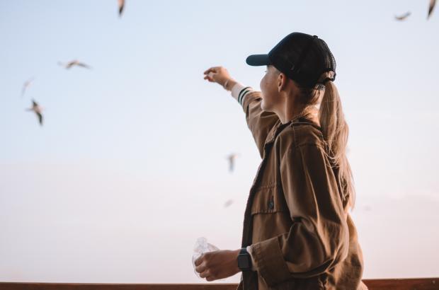 Девушка в коричневой куртке и черной кепке кормит птиц