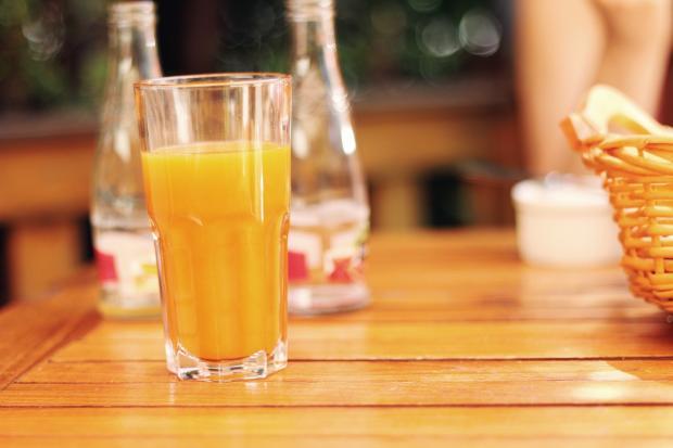 на деревянном столе стоит стакан апельсинового сока
