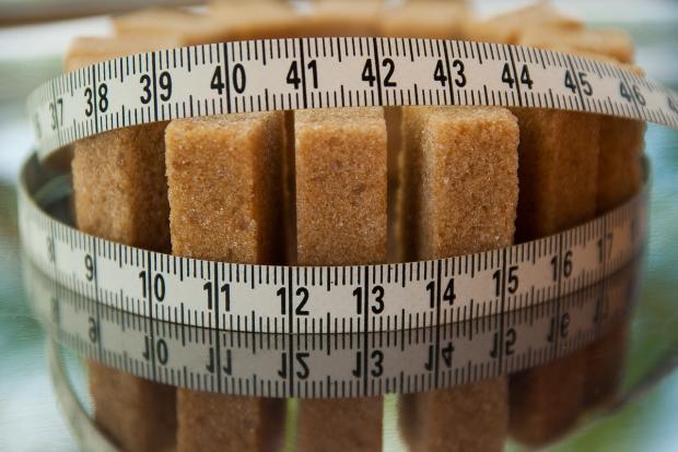 перетянутый сантиметровой лентой тростниковый сахар