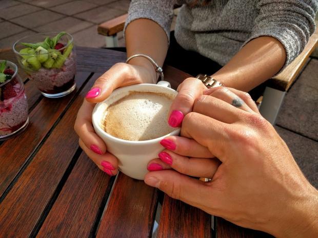 пара с чашкой кофе держится за руки