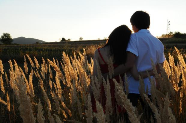обнявшаяся пара стоит в осеннем поле